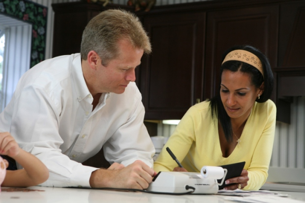 Close-up of a mid adult man looking at a mid adult woman writing with a pen
